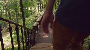 Looking Down Stairs by A Young Man In A Casual Denim Shirt And Yellow Trendy Trousers