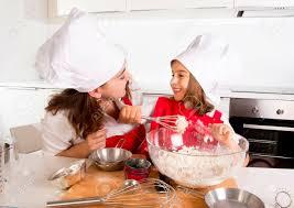 travailler en cuisine mère heureuse cuisson avec la fille en tablier et chapeau