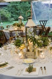 lantern centerpieces lantern centerpiece candles bamboo chairs greenery outdoor setting