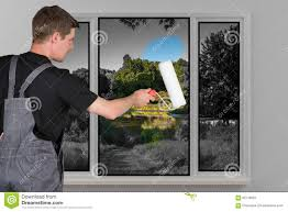 man paints back a window color with a paint roller stock photo