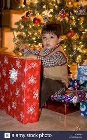 2 year old boy with christmas presents and tree mr stock photo