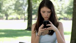 a beautiful teen is sad in the park with a cell phone video