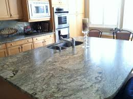 granite countertop dark wood floors with white kitchen cabinets