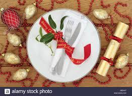 christmas dinner table setting with white porcelain plate red christmas dinner table setting with white porcelain plate red ribbon bow napkin cutlery holly mistletoe cracker baubles