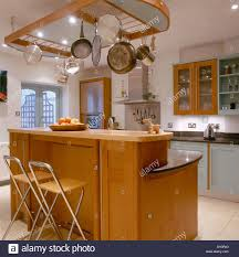 suspended pan rack above pale wood island unit with breakfast bar