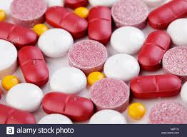 types of red colors pile of different types of pills and tablets in various shapes and
