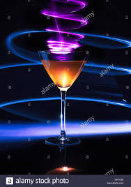 colorful cocktail in glass with light effects on dark background