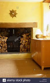 logs stored either side of wood burning stove set in inglenook