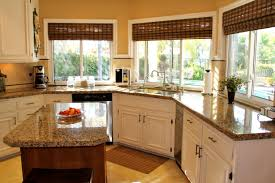 long white kitchen cabinet in front of the windows combined with