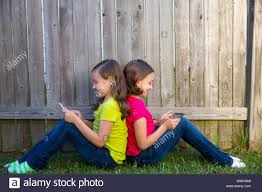 twin sister girls playing tablet pc sitting on backyard lawn stock