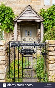 rural english stone house with wooden porch and gate with sign