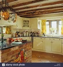 granite worktop on brick island unit in cream cottage kitchen with
