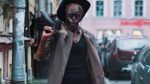 cosplayer in scary halloween makeup of ghoul in cowboy hat from
