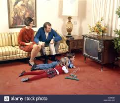 S FAMILY OF  WATCHING TELEVISION IN LIVING ROOM PARENTS ON - Family in living room