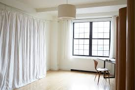 white fabric curtain divider connected by glass window with black