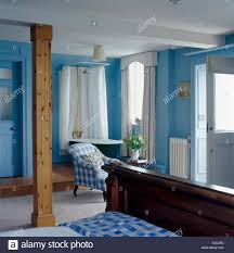 upright wooden beam in blue coastal bedroom with shower above roll