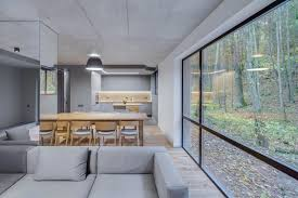 a house recessed and hidden behind a continuous concrete wall by