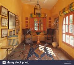 patterned rug in yellow spanish dining room with antique wooden patterned rug in yellow spanish dining room with antique wooden chairs at painted table in front