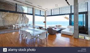 modern luxury living room and dining room open to patio with ocean