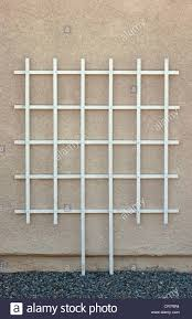 empty new white wood garden trellis by stucco wall stock photo