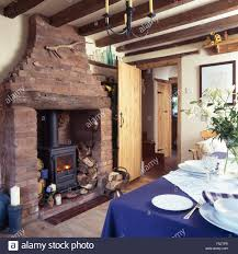 wood burning stove in exposed brick fireplace in a cottage dining