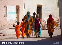 indian women and girls dressed as wedding guests walking to the