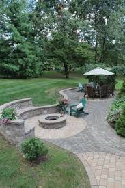 Backyard Brick Patio Design With Grill Station Seating Wall And by Natural Stone Sitting Wall With Bluestone Cap Surrounds A Fire Pit