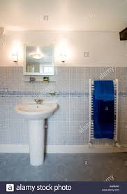 modern bathroom hand basin with mirror and wall lights and towel