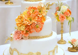 and gold wedding cake with bright peach orange yellow sugar flowers