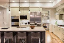 kitchen interior with island sink cabinets and hardwood floors kitchen interior with island sink cabinets and hardwood floors in new luxury home