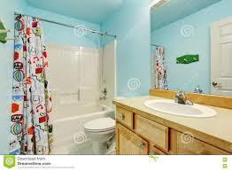 kids bathroom in blue tones with wooden cabinets and colorful