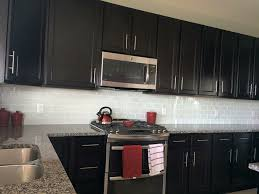black kitchen cabinets with white subway tile backsplash white glass subway tile backsplash with cabinets