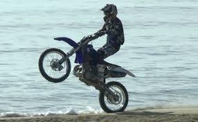 dirt bike riding shoes biker on dirt bike does wheelies on the beach youtube