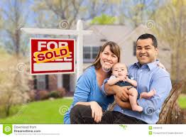 young family in front of sold real estate sign and house royalty
