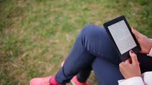 attractive smiling young woman reads e book tablet and talks to attractive young woman dressed casually uses e book tablet sitting on a wooden bench