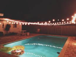 backyard evening outdoor party string lights over the pool idea