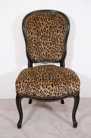 pair of antique ebonized slipper chairs with velvet leopard print