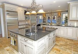 country broken white galley kitchen with black marble top storage