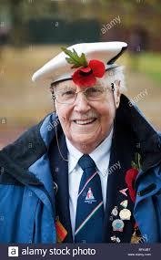 a war veteran and old soldier wearing a white beret and a poppy at