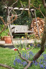 relaxing summer garden back yard with flowers and a swing bench