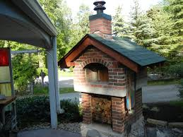 outdoor pizza oven with a gable roof and fully enclosed red brick