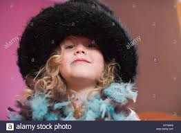 four year old tries on fancy costume hat and feather boa