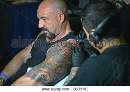 man getting a large arm tattoo at the new york tattoo convention