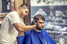 barber in white shirt trimming man u0027s hair in blue textile while