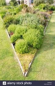 triangular raised flower bed on large garden lawn stock photo