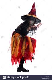 profile of a wearing a witch costume and standing on one leg