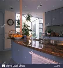 blue kitchen cabinets brown granite basket of oranges on island unit with brown granite worktop