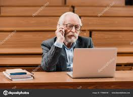 looking with grey hair grey hair professor talking smartphone looking laptop stock