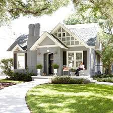 brick bungalow painted gray with white trim and black shutters