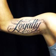 bicep tattoo of the word loyalty tattoo ideas center